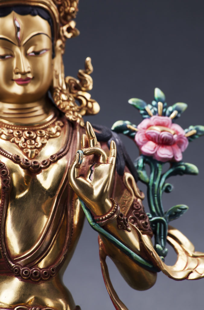 The gilded form of Green Tara with flower, made of metal. Executed in the Tibetan tradition.